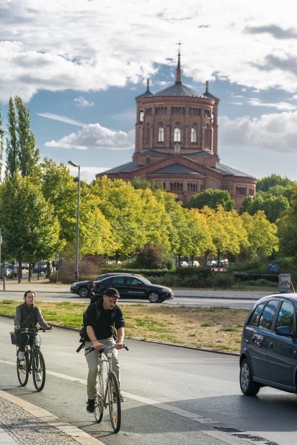 BERLIN TYSKLAND - Juli 28, 2018: Cyklister som rider på de tysta gatorna som är främsta av protestanthelgonet Thomas Church, på arkivfoton