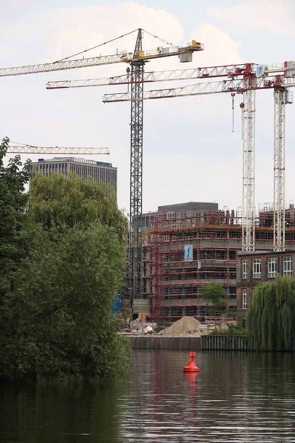 Berlin Tyskland, 13 Juni 2018 En konstruktionsplats på flodbanken i Berlin Tornkranar stiger in i himlen arkivfoto