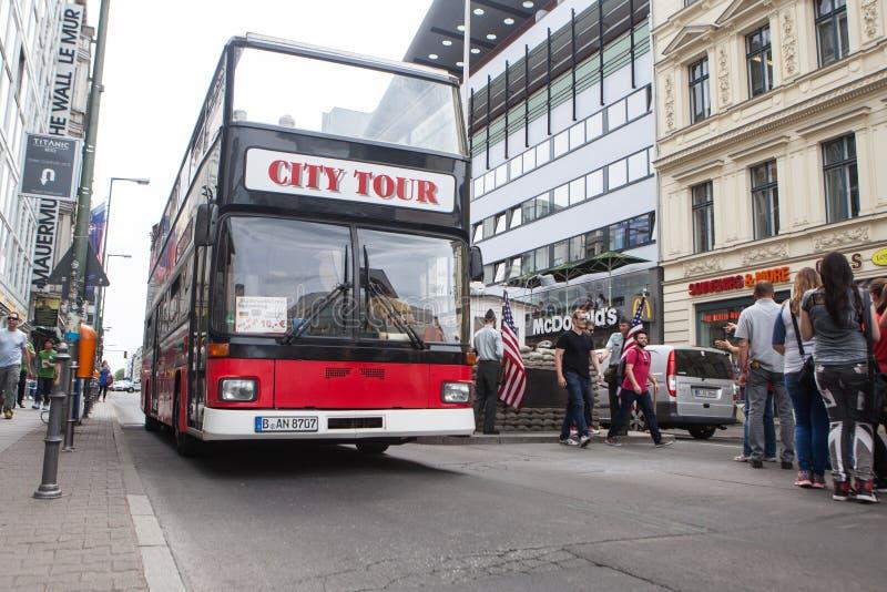 BERLIN TYSKLAND - MAJ 10, 2015: Buss på Checkpoint Charlie Korsningen punkt mellan östligt och västra - berlin blev ett symbol av royaltyfria foton