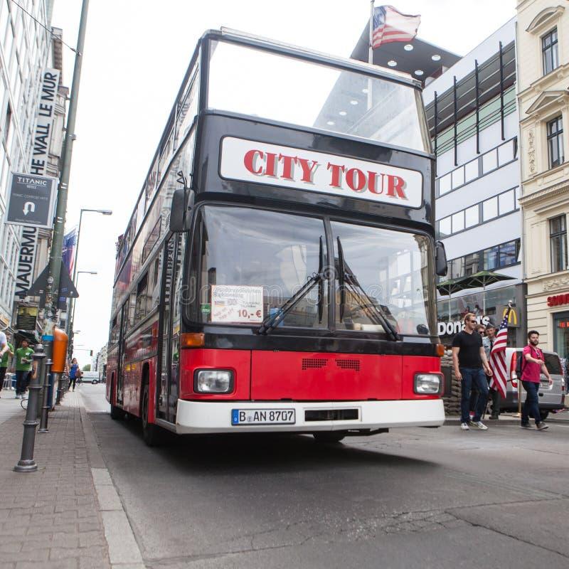 BERLIN TYSKLAND - MAJ 10, 2015: Buss på Checkpoint Charlie Korsningen punkt mellan östligt och västra - berlin blev ett symbol av arkivbilder