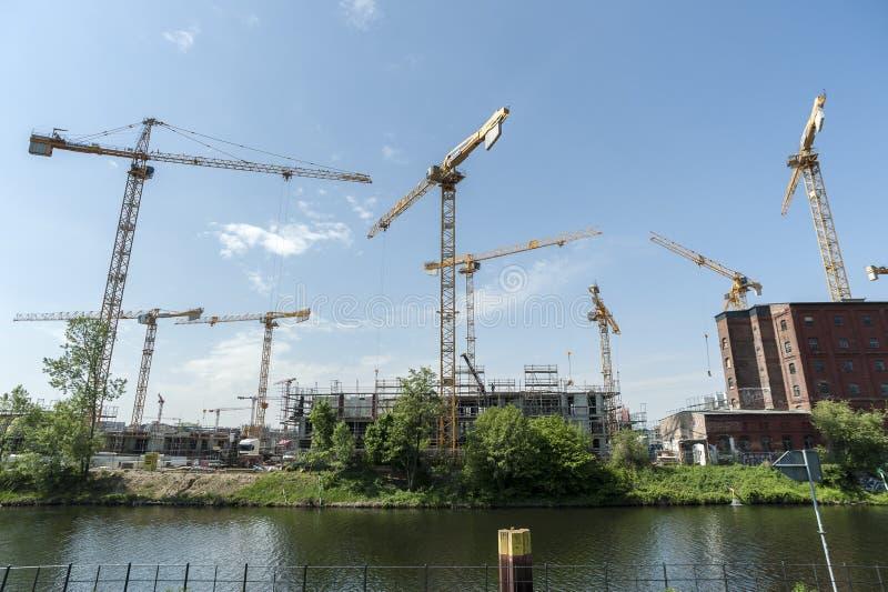 BERLIN TYSKLAND, MAJ 24, 2018: Många fungerande kranar på byggnadsplatsen i Berlin, bredvid en kanal royaltyfri fotografi