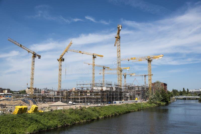 BERLIN TYSKLAND, MAJ 24, 2018: Många fungerande kranar på byggnadsplatsen i Berlin, bredvid en kanal arkivbild