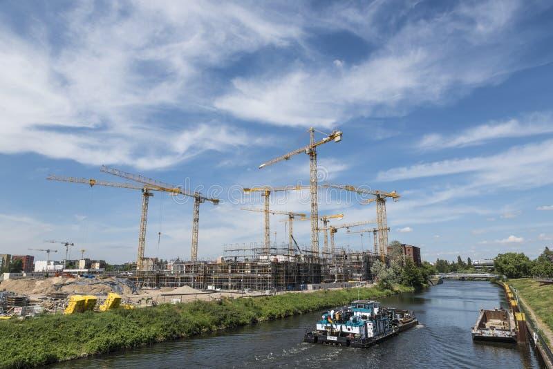 BERLIN TYSKLAND, MAJ 24, 2018: Många fungerande kranar på byggnadsplatsen i Berlin, bredvid en kanal arkivfoto