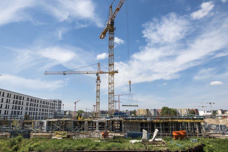 BERLIN TYSKLAND, MAJ 24, 2018: Många fungerande kranar på byggnadsplatsen i Berlin, bredvid en kanal royaltyfria bilder