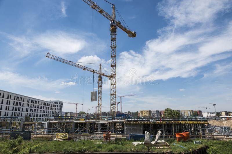 BERLIN TYSKLAND, MAJ 24, 2018: Många fungerande kranar på byggnadsplatsen i Berlin, bredvid en kanal fotografering för bildbyråer