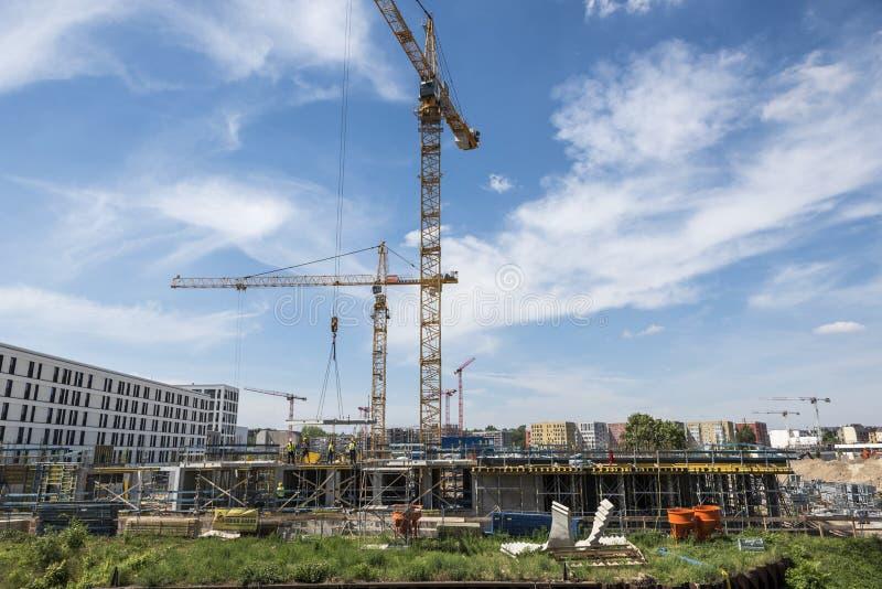 BERLIN TYSKLAND, MAJ 24, 2018: Många fungerande kranar på byggnadsplatsen i Berlin, bredvid en kanal arkivbilder