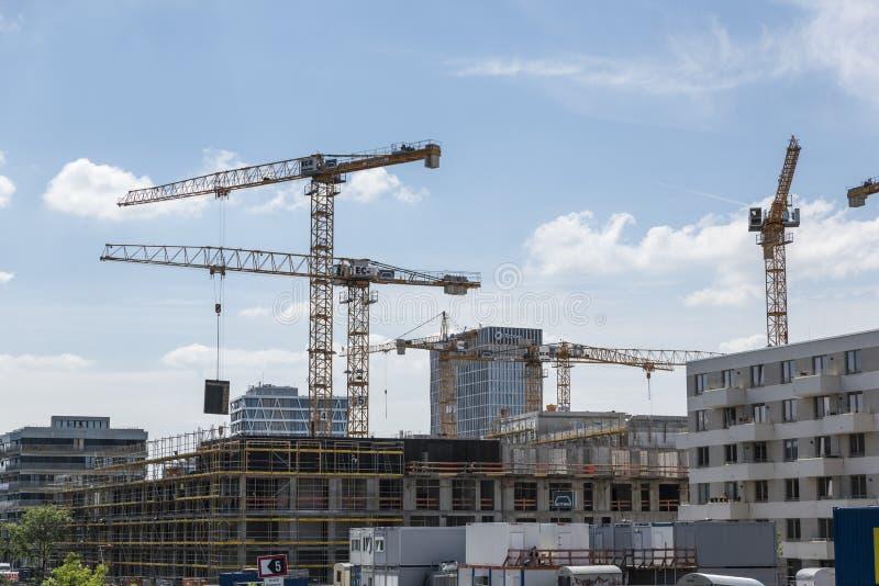 BERLIN TYSKLAND, MAJ 24, 2018: Många fungerande kranar på byggnadsplatsen i Berlin, bredvid en kanal arkivfoton