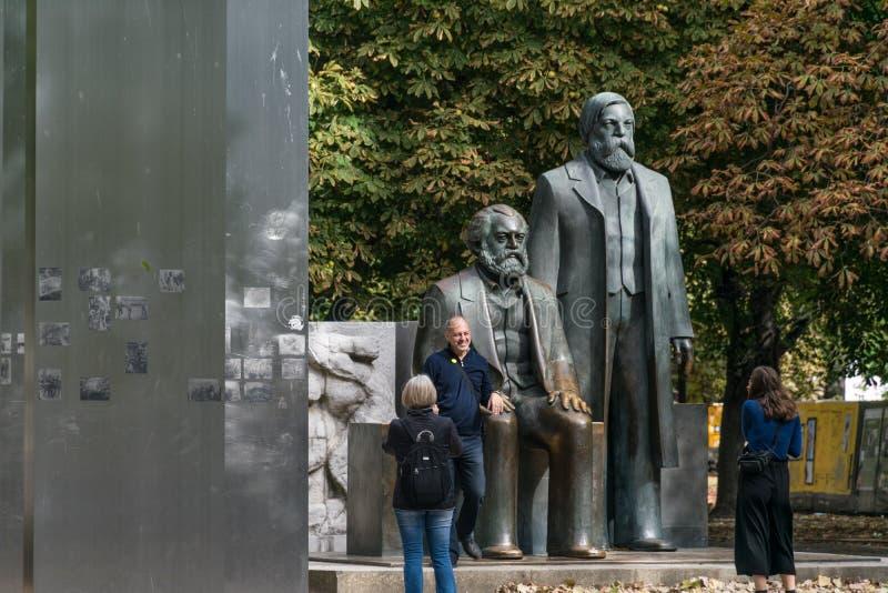 BERLIN TYSKLAND - September 26, 2018: Turister som tar bilder nära statyerna av Karl Marx och Friedrich Engels royaltyfri foto
