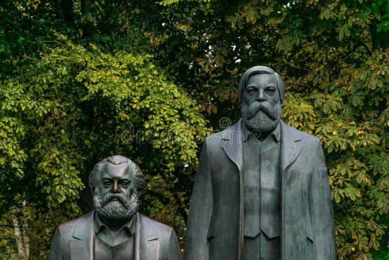 BERLIN TYSKLAND - September 26, 2018: In zoomar statyerna av Karl Marx och Friedrich Engels, intellektuellerna av arkivbilder