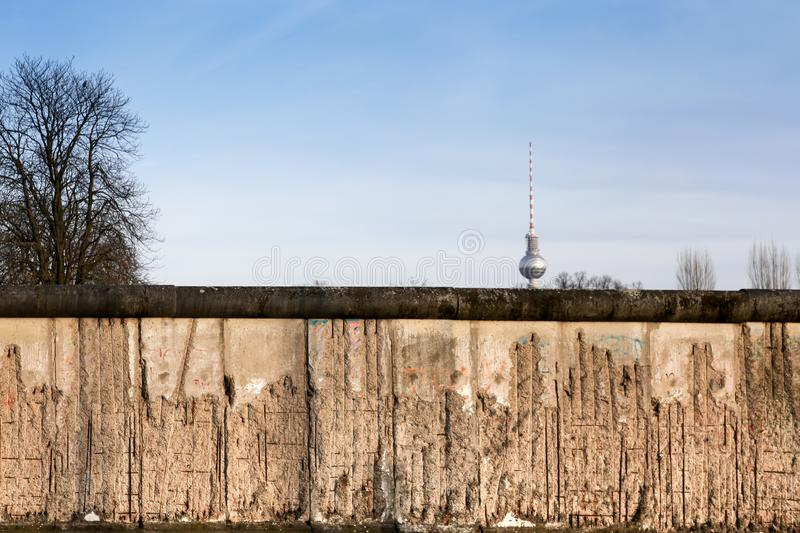 Berlin Wall original weathered section damaged with exposed iron bars partly covering the TV tower Berliner Fernsehturm far royalty free stock photo