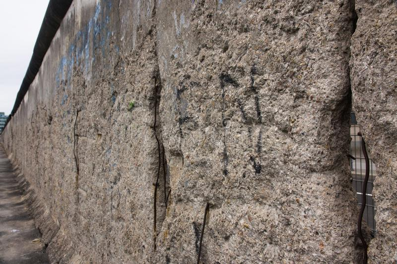 Berlin Wall original weathered section damaged with exposed iron bars and rough cement concrete texture royalty free stock photo