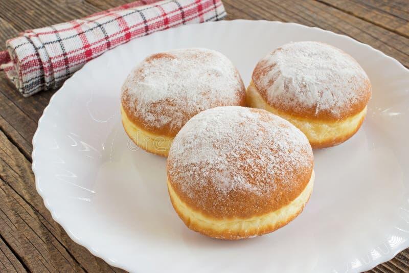 Berliner Donuts auf Teller auf Holztisch stockfoto