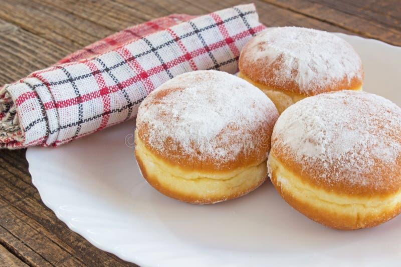Berliner Donuts auf Teller auf Holztisch lizenzfreies stockfoto