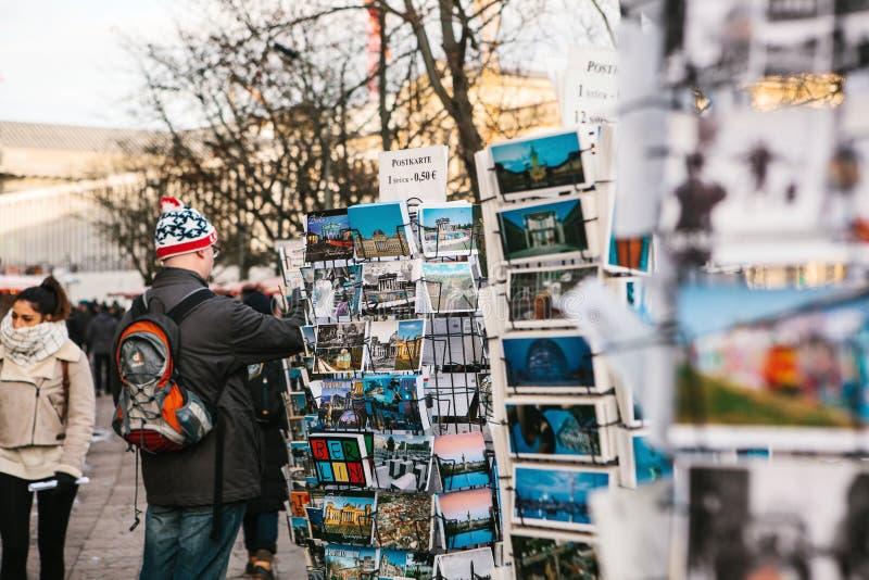 Berlino, Germania 15 febbraio 2018: Vendita della via delle cartoline e dei ricordi Il compratore sceglie una carta per la memori immagini stock libere da diritti
