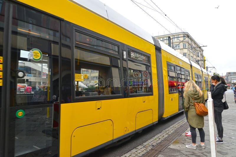Berlino, Germania I costi gialli del tram ad una fermata fotografia stock