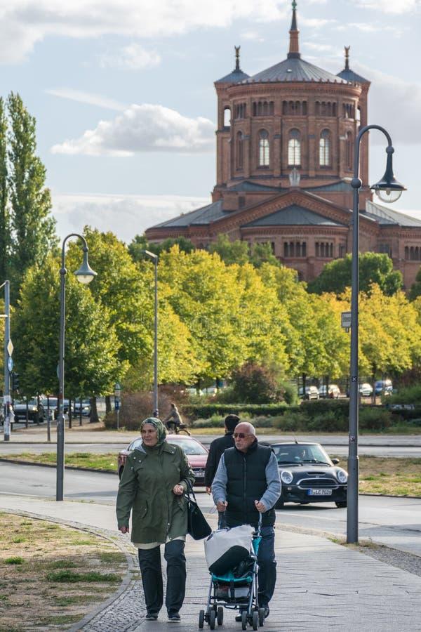 BERLINO, GERMANIA - 28 luglio 2018: Accoppi degli anziani che camminano in un marciapiede con un passeggiatore di bambino vicino  fotografie stock libere da diritti