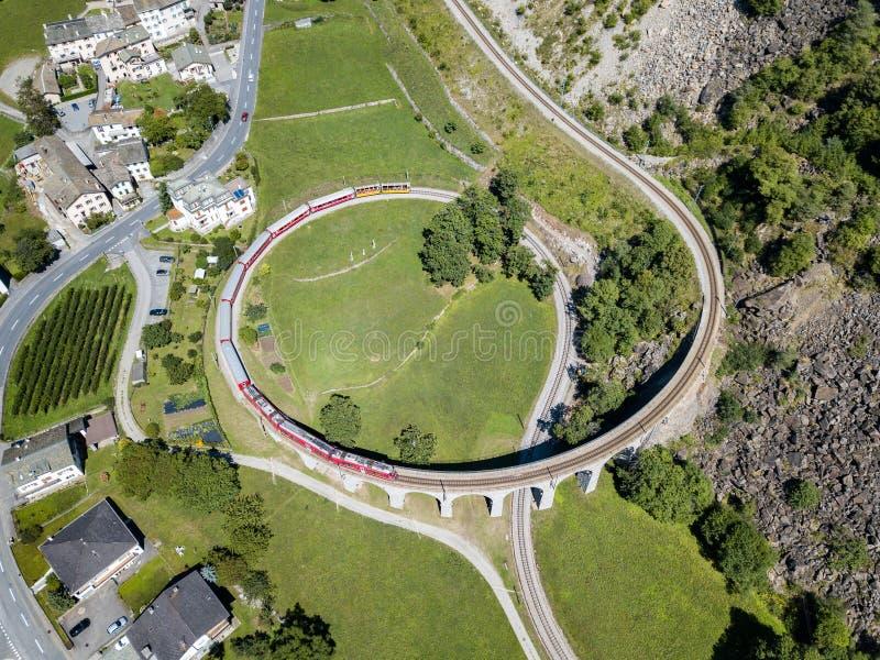 Bernina Express is going through the famous circular viaduct in Swiss Alps mountain stock photos