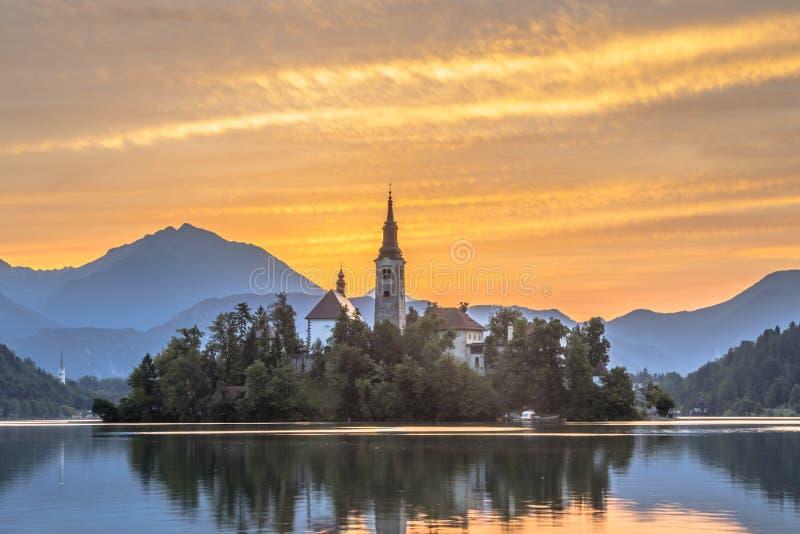 Beroemd die Meer met kerk onder oranje ochtendhemel wordt afgetapt stock foto's