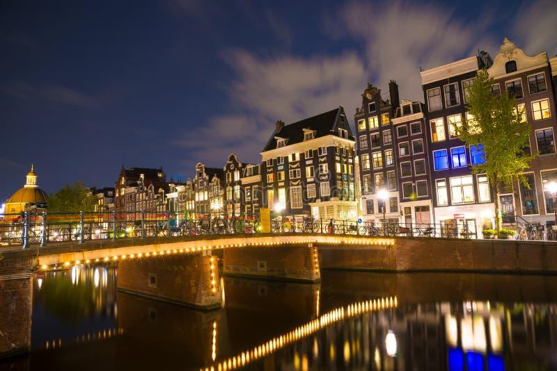 Beroemde Amstel-rivier en nachtmening van de mooie stad van Amsterdam nederland stock afbeelding