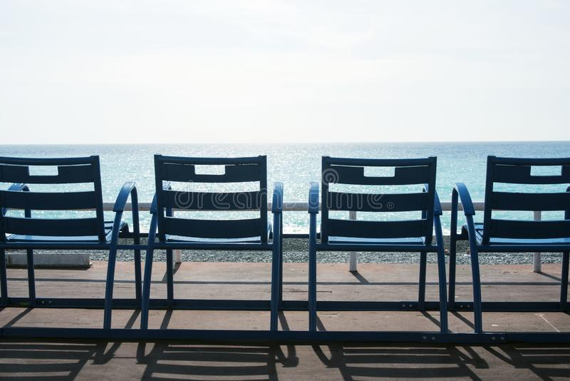 Beroemde blauwe stoelen op Promenade des Anglais van Nice, Frankrijk tegen de achtergrond van het blauwe overzees stock afbeeldingen