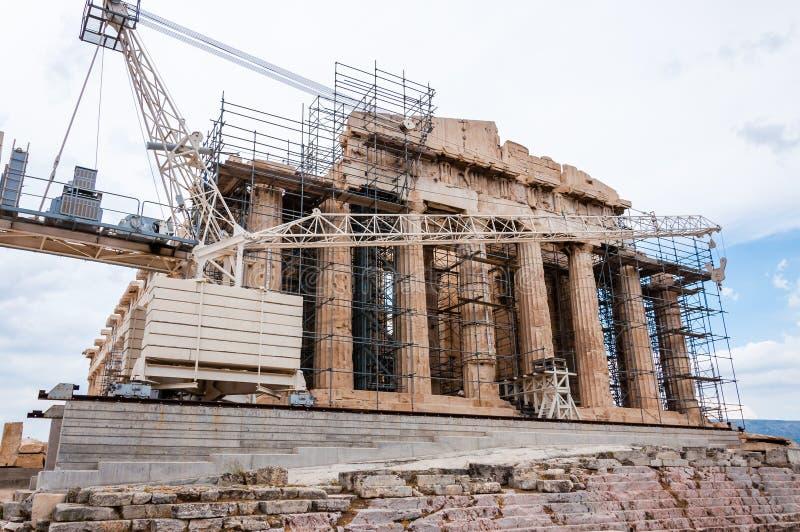 Beroemde die Parthenon op Akropolisheuvel onder wederopbouw door steiger en status grote bouwkraan wordt omringd in stock afbeelding