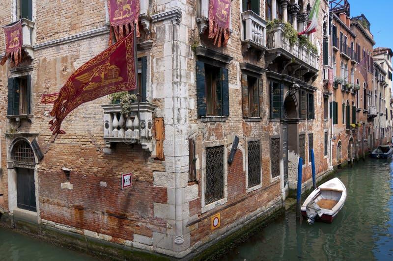 Beroemde smalle het kanaalmening van Venetië met baksteengebouwen, vlaggen met stock foto