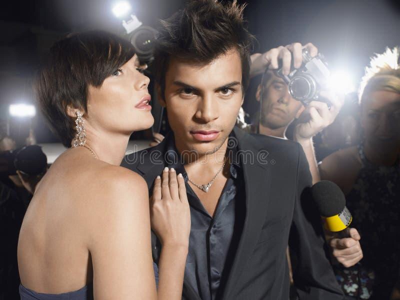 Beroemdheidspaar door Paparazzi wordt omringd die royalty-vrije stock afbeelding