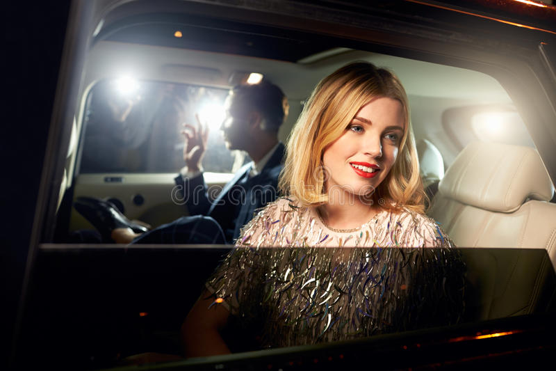 Beroemdheidspaar in rug van een auto, door paparazzi wordt gefotografeerd die royalty-vrije stock foto's