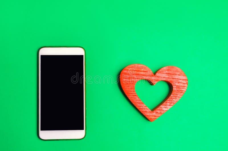 Beroende på sociala nätverk ringa smartphonen och hjärta på en grön bakgrund online-datummärkning, flörta, meddelande och som kal royaltyfria bilder