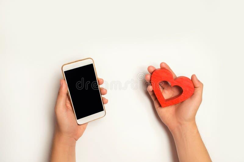 Beroende på sociala nätverk telefonsmartphone och hjärta i händer online-datummärkning, flörta, meddelande och som kallar ditt äl royaltyfri foto