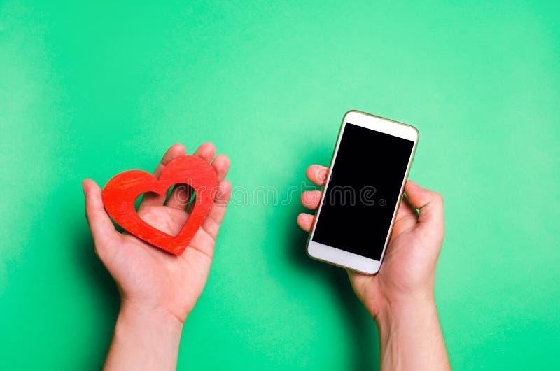Beroende på sociala nätverk telefonsmartphone och hjärta i händer online-datummärkning, flörta, meddelande och som kallar ditt äl royaltyfria foton