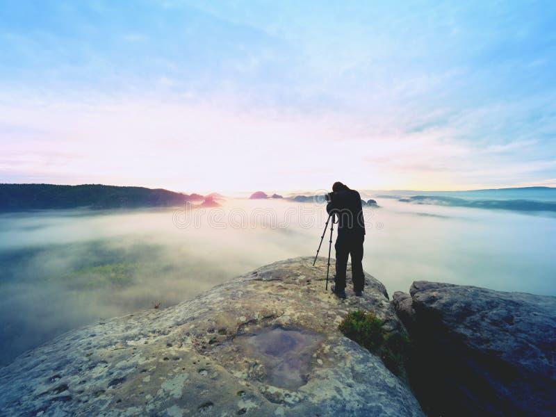 Beroeps op klip De aardfotograaf neemt foto's met spiegelcamera op piek van rots Dromerige mist stock afbeelding