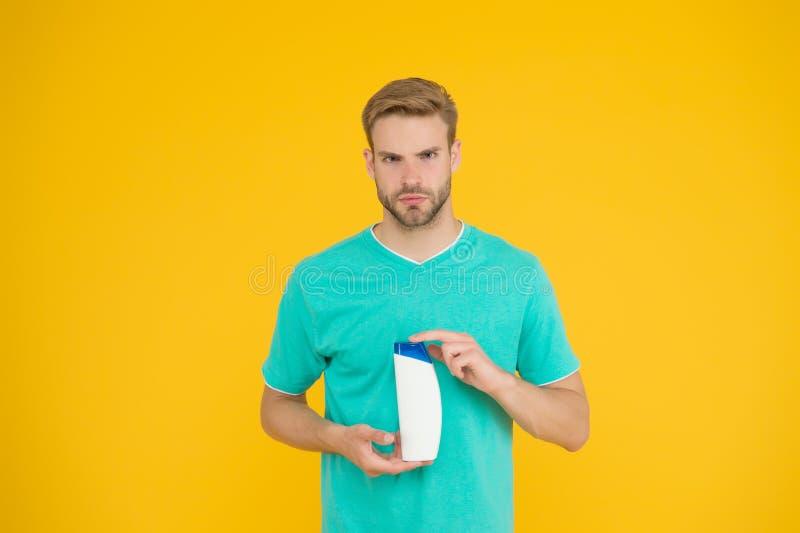 Beroepsbarber Cosmetische producten voor douche of bad Beared man hold gel tube Barbershop Knap stock foto