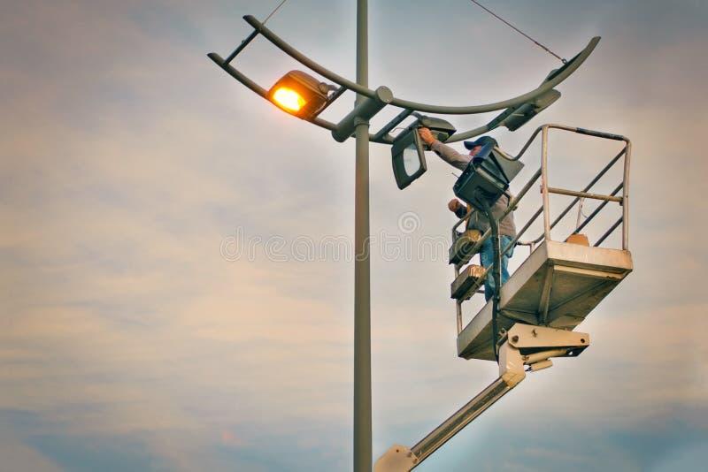 Beroepsreparatie en onderhoud van straatlantaarns - de kraan hief een elektricien op om bollen bij zonsondergang in avond te verv stock fotografie