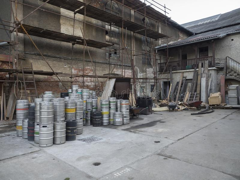 Beroun, Czech Republic, March 23, 2019: courtyard of Beroun brewery called Berounsky medved with pile of empty metal. Barrels or kegs of czech beer, copy space royalty free stock photography