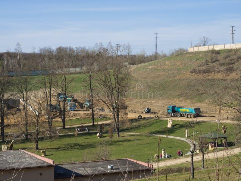 Beroun, República Checa, o 23 de março de 2019: Vista no terreno de construção da construção e no parque público com os ca fotografia de stock royalty free