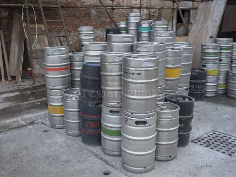 Beroun Tjeckien, mars 23, 2019: slut upp Pilled tomma metalltrummor eller kaggar av tjeckiskt öl på gård längs av tegelsten royaltyfri foto