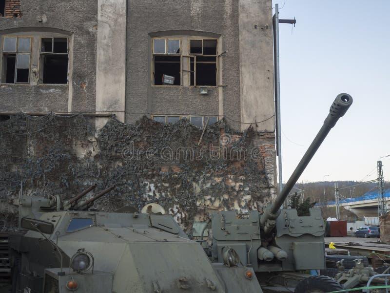 Beroun Tjeckien, mars 23, 2019: tv? bev?pnade den gamla milit?ra bilbeh?llaren i framdel av ?vergiven tom retro tappninggrunge royaltyfri fotografi