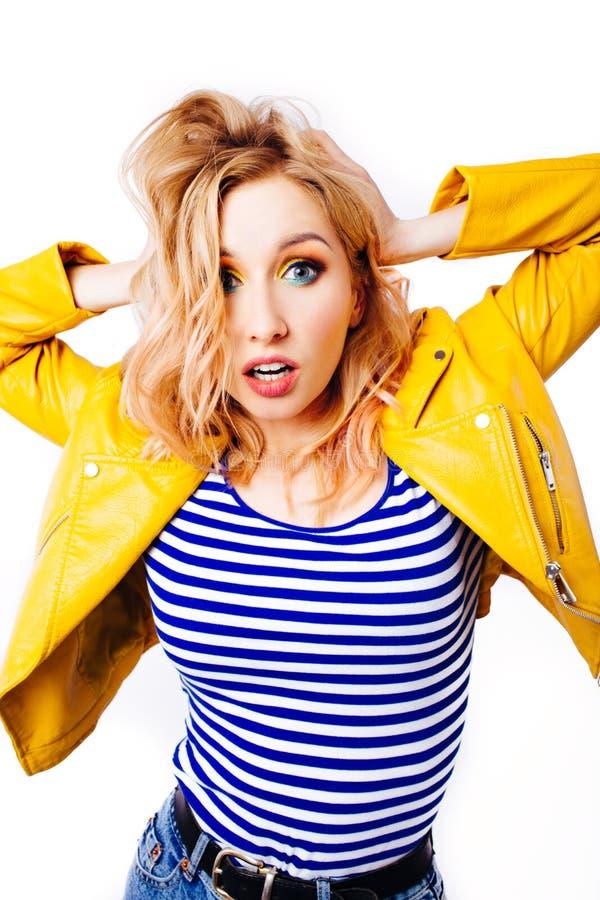 ?berraschte Blondine des jungen M?dchens in einer gelben hellen Jacke betrachtet den Zuschauer lizenzfreie stockbilder
