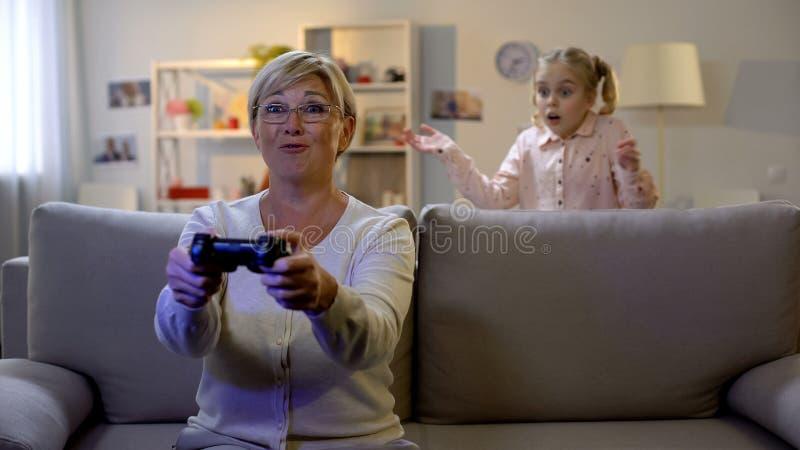 ?berraschte Enkelin, welche die Oma spielt Videospiel nachts, Sucht betrachtet lizenzfreies stockfoto