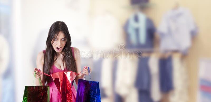 ?berraschte Frau, die das Einkaufen betrachtet stockbild
