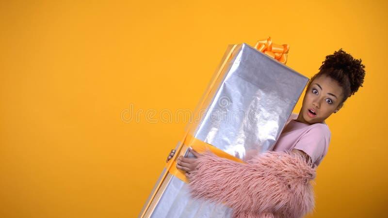 ?berraschte Frau, die gro?es giftbox, zum T?rZustelldienst, gelber Hintergrund h?lt lizenzfreie stockfotos