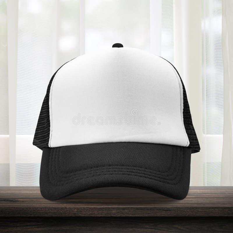 Berretto nero fatto dal materiale del tessuto sul fondo dello spogliatoio con stile dei berretti da baseball del modello Posto bi immagine stock