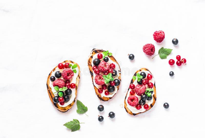 Berries bruschetta on a light background, top view. Sandwiches with cream cheese, raspberries, red and black currants. Delicious b royalty free stock images