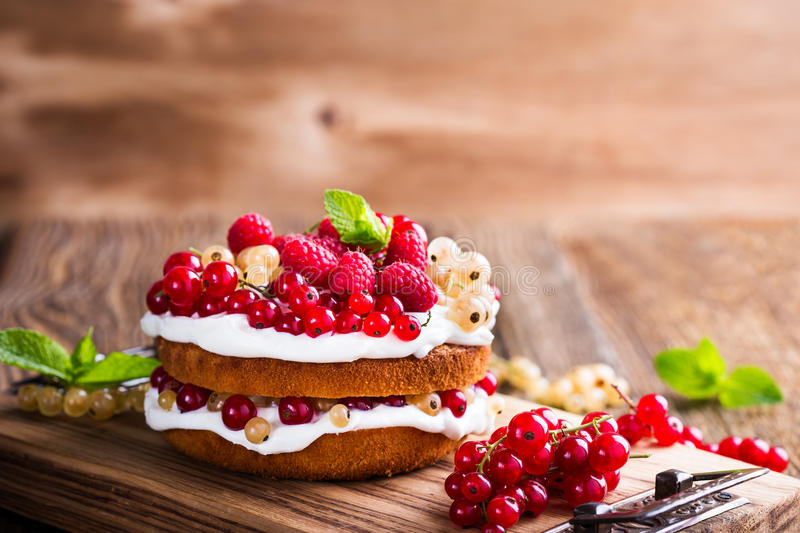 Berries butter layer cake with whipped cream topping. Homemade butter layer cake with whipped cream topping on rustic wooden table stock photography