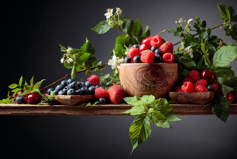 Berries closeup colorful assorted mix of strawberry, blueberry, raspberry and sweet cherry on a old wooden table royalty free stock image