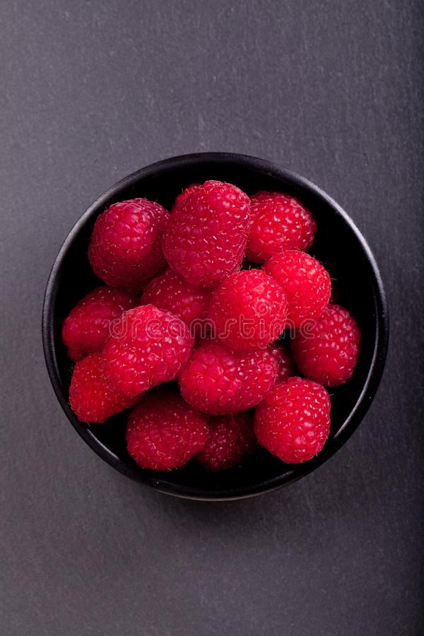 Berries in a cup. Raspberries in a black cup royalty free stock images