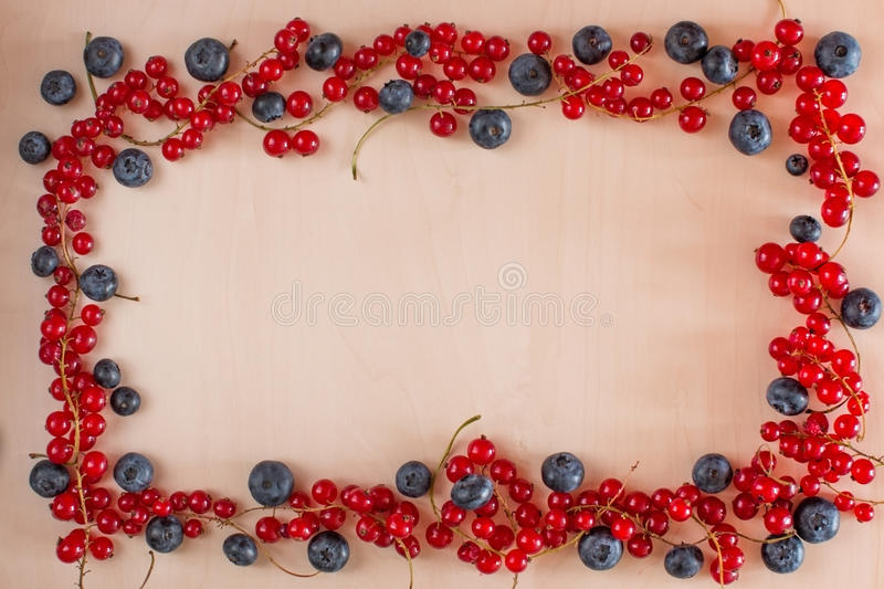 Berries Frame on Wooden Background. Blueberries, red currants royalty free stock photo