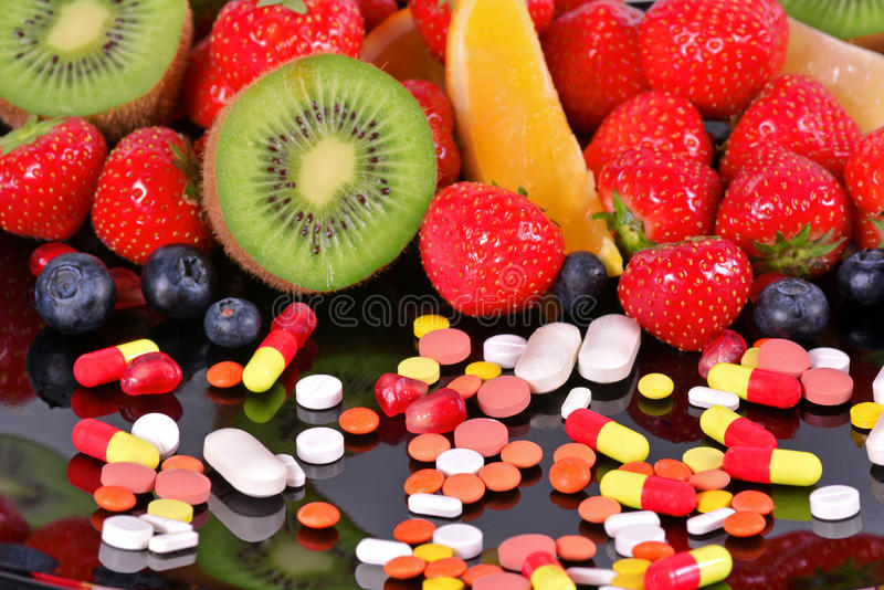 Berries, fruits, vitamins and nutritional supplements royalty free stock photos