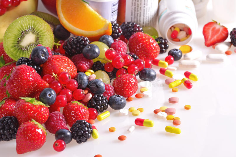 Berries, fruits, vitamins and nutritional supplements stock image